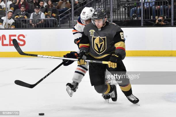 Jonathan Marchessault of the Vegas Golden Knights and Brandon Davidson of the Edmonton Oilers skate to a loose puck during the game at TMobile Arena...