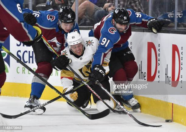 Jonathan Marchessault of the Vegas Golden Knights battles Nikita Zadorov and Nazem Kadri of the Colorado Avalanche for the puck during the third...