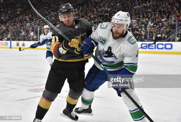 Jonathan Marchessault of the Vegas Golden Knights battles Oscar Fantenberg of the Vancouver Canucks during the first period at TMobile Arena on...