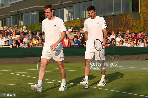 Jonathan Marray and Colin Fleming of Great Britain walk back to their seats during a break in the Gentlemen's Doubles first round match between Colin...