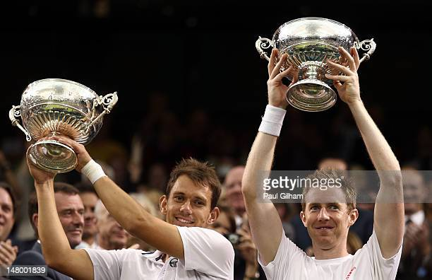 Jonathan Marray of Great Britain and Frederik Nielsen of Denmark lift their winners trophies after winning their Gentleman's Doubles final match...