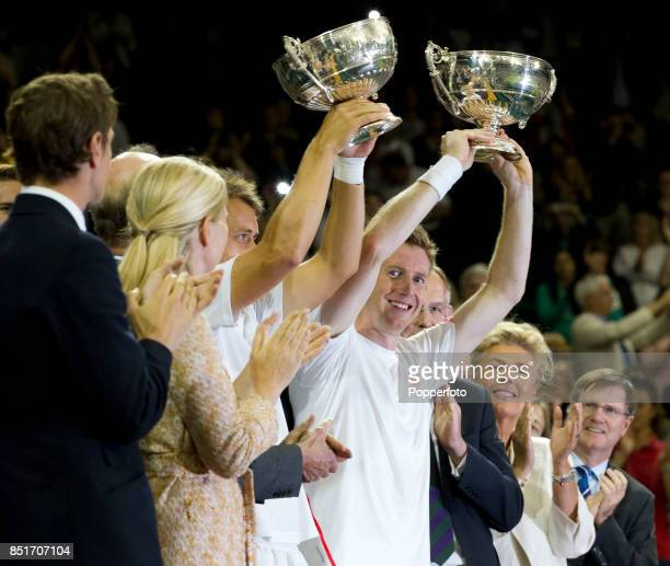 Jonathan Marray of Great Britain and Frederik Nielsen of Denmark lift their trophies after winning their Gentlemans Doubles final match against...