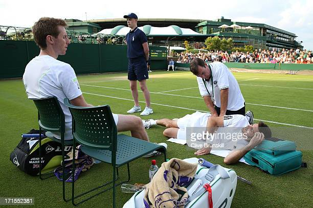 Jonathan Marray of Great Britain watches as his teammate Colin Fleming of Great Britain receives treatment during a break in their Gentlemen's...