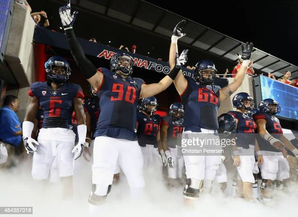 Jonathan McKnight Dan Pettinato and Mickey Baucus of the Arizona Wildcats prepare to take the field with teammates before the college football game...