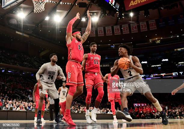 Jonathan Mulmore of the Georgetown Hoyas drives to the basket against Marvin Clark II and Tariq Owens of the St John's Red Storm during the first...