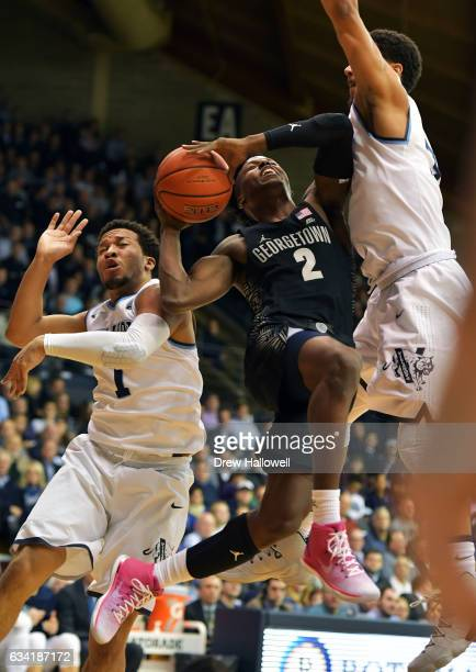 Jonathan Mulmore of the Georgetown Hoyas tries to squeeze a layup between Jalen Brunson and Josh Hart of the Villanova Wildcats at The Pavilion on...
