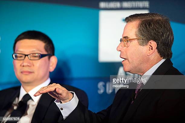 Jonathan Nelson chief executive officer of Providence Equity Partners Inc right gestures as he speaks while Lim Chow Kiat chief investment officer of...