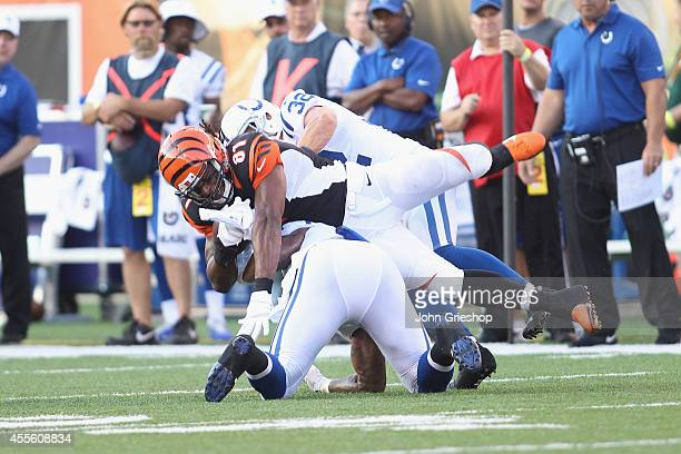 Jonathan Newsome and Colt Anderson of the Indianapolis Colts tackle Alex Smith of the Cincinnati Bengals during their game at Paul Brown Stadium on...