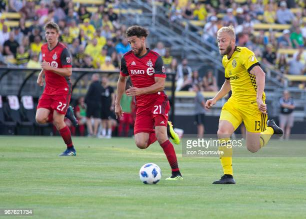 Jonathan Osorio of Toronto FC and Mike Grella of Columbus Crew SC chase the loose ball during the game between the Columbus Crew SC and the Toronto...
