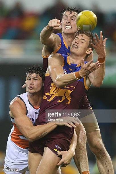 Jonathan Patton of the Giants and Darcy Gardiner and Matthew Hammelmann of the Lions compete for the ball during the round 17 AFL match between the...