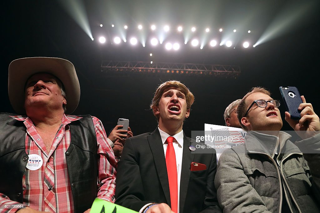 Jonathan Pozzie (C) and other supporters watch Republican presidential nominee Donald Trump speak during a campaign rally at the SNHU Arena November 7, 2016 in Manchester, New Hampshire. With less than 24 hours until Election Day in the United States, Trump and his opponent, Democratic presidential nominee Hillary Clinton, are campaigning in key battleground states that each must win to take the White House.