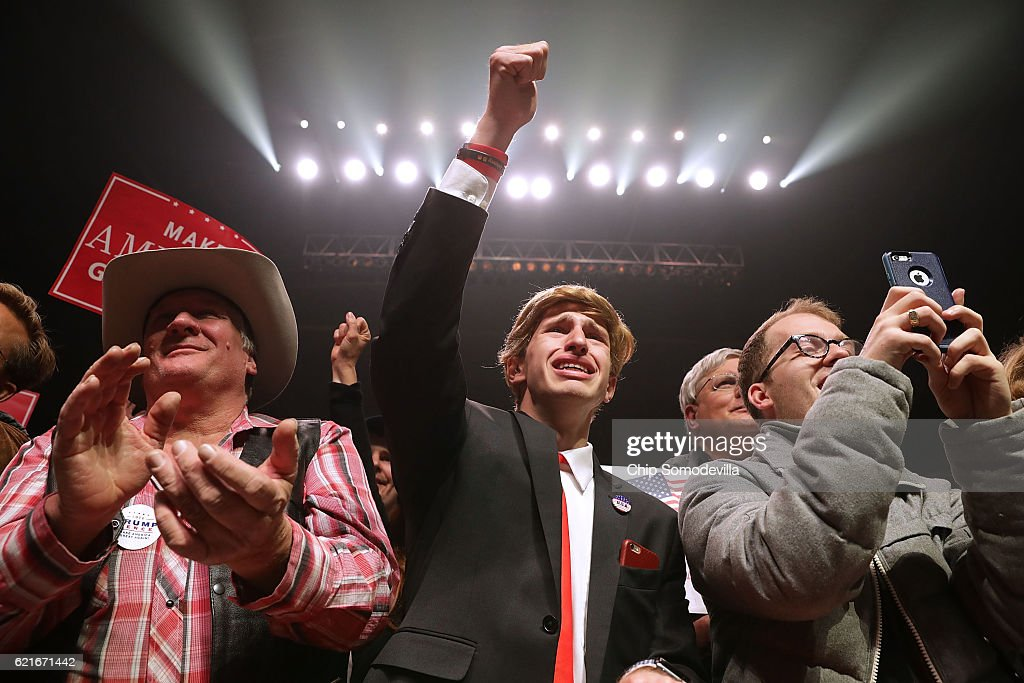 Jonathan Pozzie (C) pumps his fist in the air as he watches Republican presidential nominee Donald Trump speak during a campaign rally at the SNHU Arena November 7, 2016 in Manchester, New Hampshire. With less than 24 hours until Election Day in the United States, Trump and his opponent, Democratic presidential nominee Hillary Clinton, are campaigning in key battleground states that each must win to take the White House.