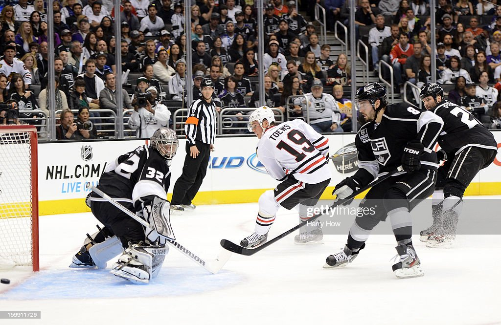 Jonathan Quick #32 and Drew Doughty #8 of the Los Angeles Kings watch as the puck crosses the goal line in front of Jonathan Toews #19 of the Chicago Blackhawks for a Marian Hossa #81 goal at Staples Center on January 19, 2013 in Los Angeles, California.