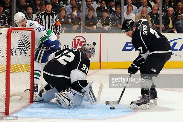 Jonathan Quick and Rob Scuderi of the Los Angeles Kings try to clear the puck against Henrik Sedin of the Vancouver Canucks in Game Three of the...