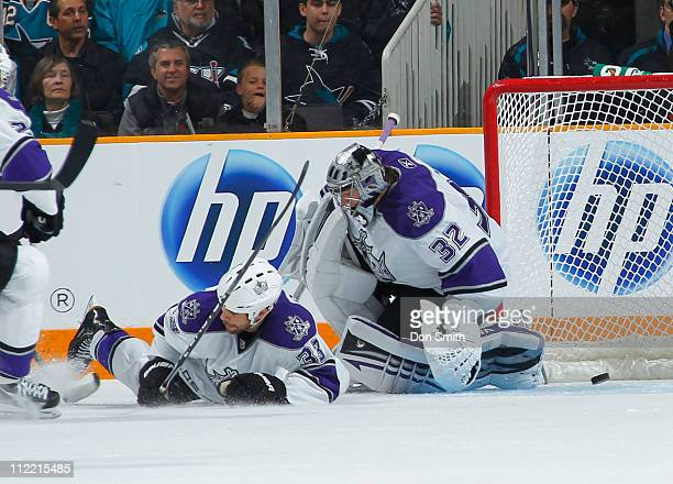 Jonathan Quick and Willie Mitchell of the Los Angeles Kings hear the horn sound as Logan Couture of the San Jose Sharks scores a goal in Game 1 of...