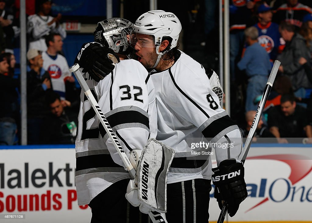 Jonathan Quick #32 of the Los Angeles Kings is congratulated by Drew Doughty #8 after defeating the New York Islanders at Nassau Veterans Memorial Coliseum on March 26, 2015 in Uniondale, New York. The Los Angeles Kings defeated the New York Islanders 3-2.
