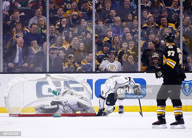 Jonathan Quick of the Los Angeles Kings is covered up by the goal in front of teammate Jake Muzzin in the second period against the Boston Bruins...