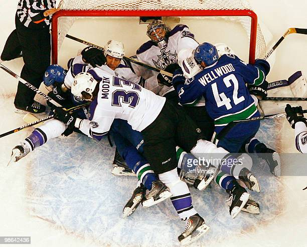 Jonathan Quick of the Los Angeles Kings lays in his crease as members of the Kings and the Canucks pile on him in his crease in Game Five of the...