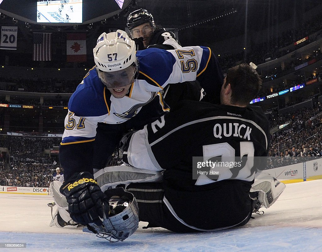 Jonathan Quick #32 of the Los Angeles Kings loses his mask as David Perron #57 of the St. Louis Blues crashes the net in front of Drew Doughty #8 during the third period in a 1-0 win over the St. Louis Blues in Game Three of the Western Conference Quarterfinals during the 2013 NHL Stanley Cup Playoffs at Staples Center on May 4, 2013 in Los Angeles, California.