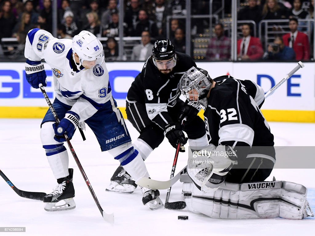 Jonathan Quick #32 of the Los Angeles Kings makes a save as Vladislav Namestnikov #90 of the Tampa Bay Lightning and Drew Doughty #8 reach for a rebound at Staples Center on November 9, 2017 in Los Angeles, California.
