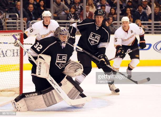 Jonathan Quick of the Los Angeles Kings makes a save in front of Rob Scuderi as Corey Perry and Ryan Getzlaf of the Anaheim Ducks skate in for a...
