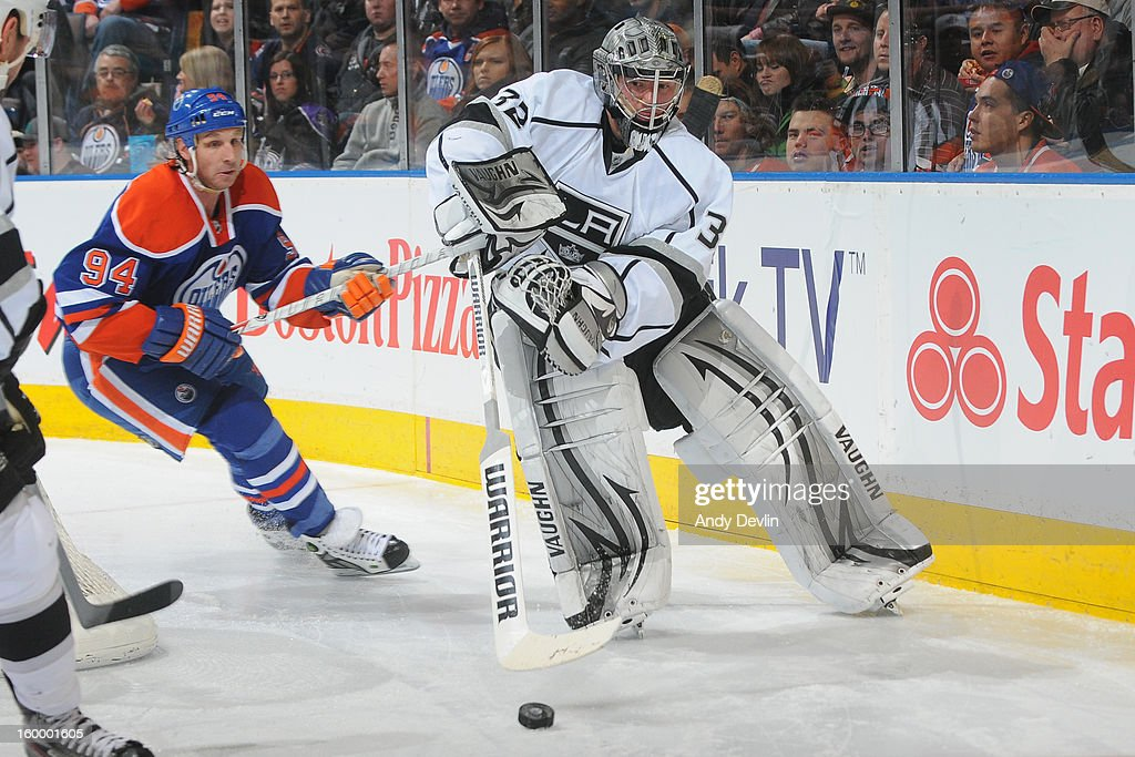 Jonathan Quick #32 of the Los Angeles Kings plays the puck behind the net against Ryan Smyth #94 of the Edmonton Oilers at Rexall Place on January 24, 2013 in Edmonton, Alberta, Canada.