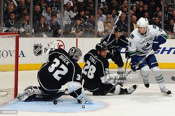 Jonathan Quick of the Los Angeles Kings reaches to make the save while teammate Jarret Stoll tries to stop Steve Bernier of the Vancouver Canucks in...