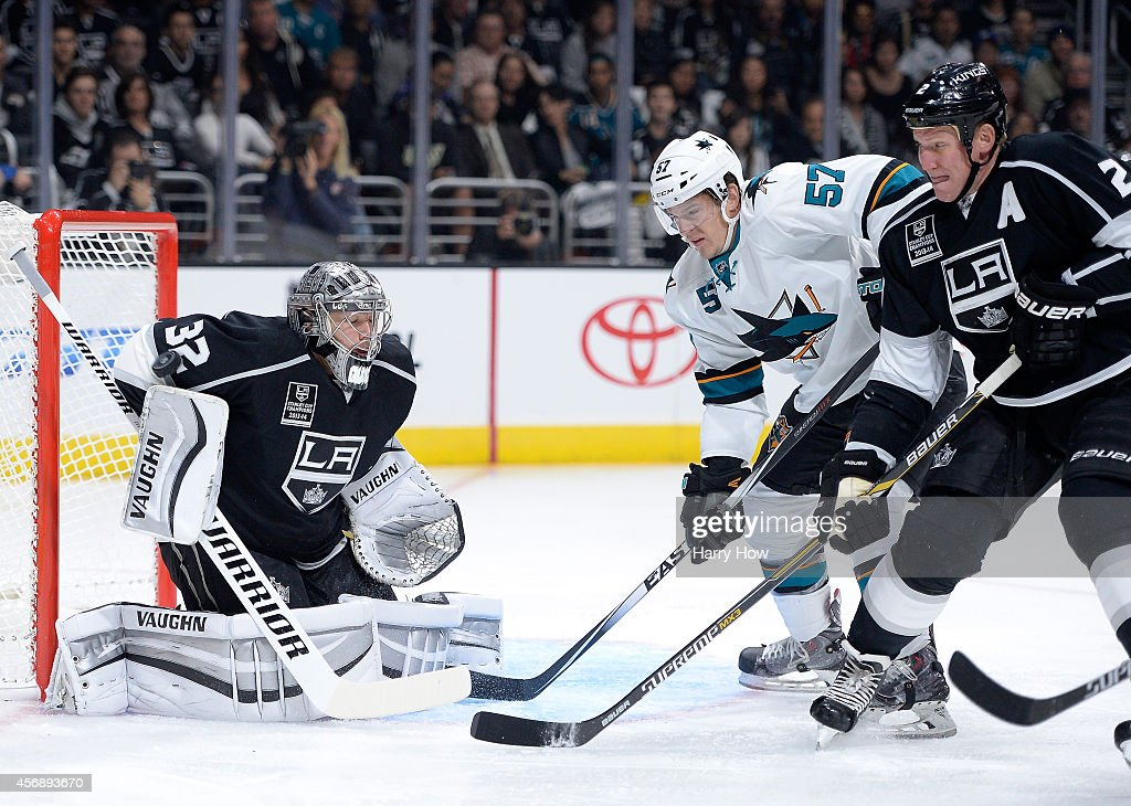 Jonathan Quick #32 of the Los Angeles Kings reacts to a shot in front of Tommy Wingels #57 of the San Jose Sharks and Matt Greene #2 of the Los Angeles Kings during the first period at Staples Center on October 8, 2014 in Los Angeles, California.