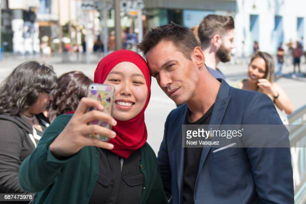 Jonathan Rhys Meyers takes a selfie with a fan at Extra at Universal Studios Hollywood on May 23 2017 in Universal City California