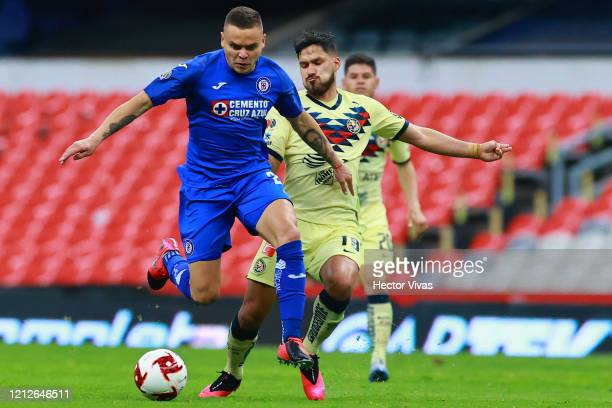 Jonathan Rodriguez of Cruz Azul struggles for the ball against Bruno Valdez of America during the 10th round match between America and Cruz Azul as...