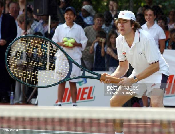 Jonathan Ross in action with an oversized racket during his match against Tim Henman at the smashed Ariel Champions of the Future celebrity tennis...
