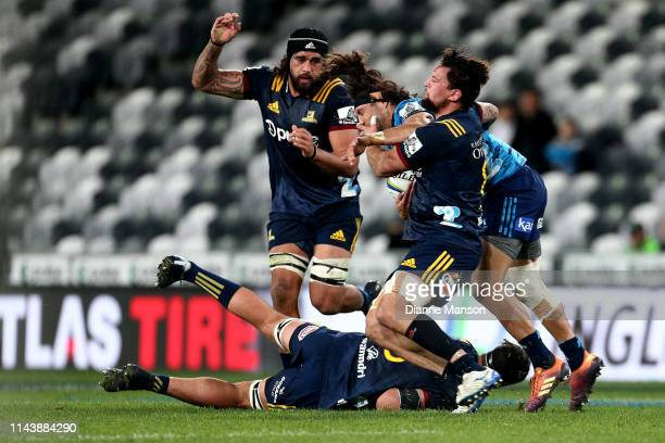 Jonathan Ruru of the Blues is tackled by Elliot Dixon of the Highlanders during the round 10 Super Rugby match between the Highlanders and the Blues...