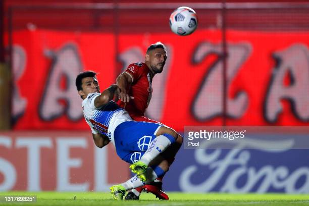 Jonathan Sandoval of Argentinos Juniors fights for the ball with Edson Puch of Universidad Catolica during a match between Argentinos Juniors and...