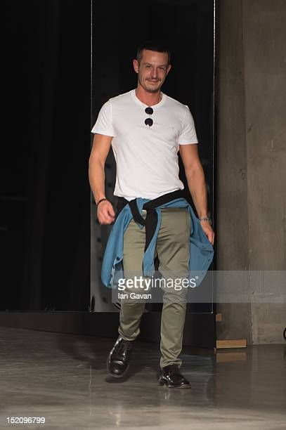 Jonathan Saunders appears at the end of the catwalk after his fashion show on day 3 of London Fashion Week Spring/Summer 2013, at the Tate Modern on...
