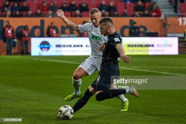 Jonathan Schmid of Augsburg and Ante Rebic of Frankfurt battle for the ball during the Bundesliga match between FC Augsburg and Eintracht Frankfurt...