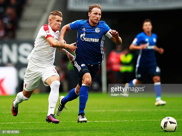 Jonathan Schmid of Augsburg is challenged by Benedikt Hoewedes of Schalke 04 during the Bundesliga match between FC Augsburg and FC Schalke 04 at WWK...