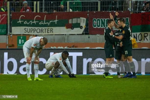 Jonathan Schmid of FC Augsburg and Sergio Cordova of FC Augsburg look dejected while players of VfL Wolfsburg celebrate after winning during the...