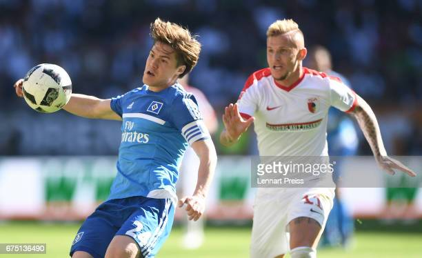 Jonathan Schmid of FC Augsburg challenges Gotoku Sakai of Hamburger SV during the Bundesliga match between FC Augsburg and Hamburger SV at WWK Arena...