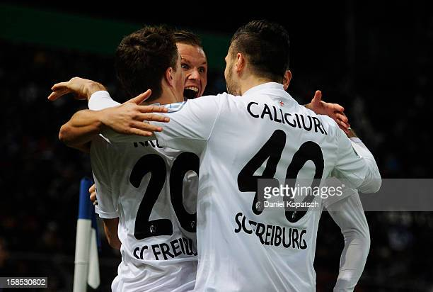Jonathan Schmid of Freiburg celebrates his team's first goal with team mates Max Kruse and Daniel Caligiuri during the DFB Cup match between...