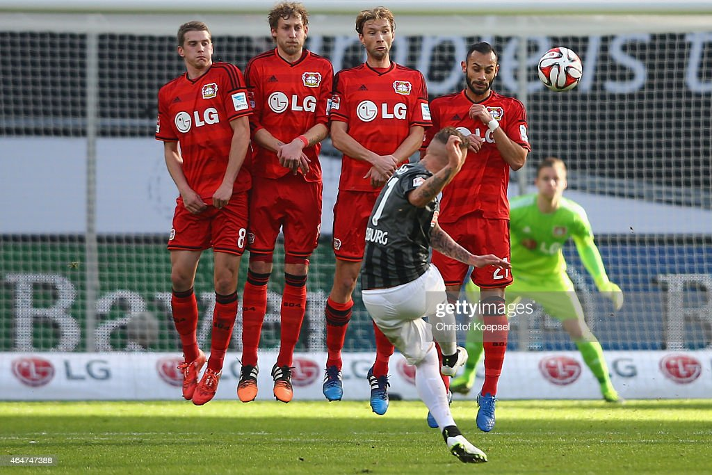 Jonathan Schmid of Freiburg shoots a free-kick of the wall of Lars Bender (L-R) Stefan Kiessling, Simon Rolfes and Karim Bellarabi during the Bundesliga match between Bayer 04 Leverkusen and SC Freiburg at BayArena on February 28, 2015 in Leverkusen, Germany.
