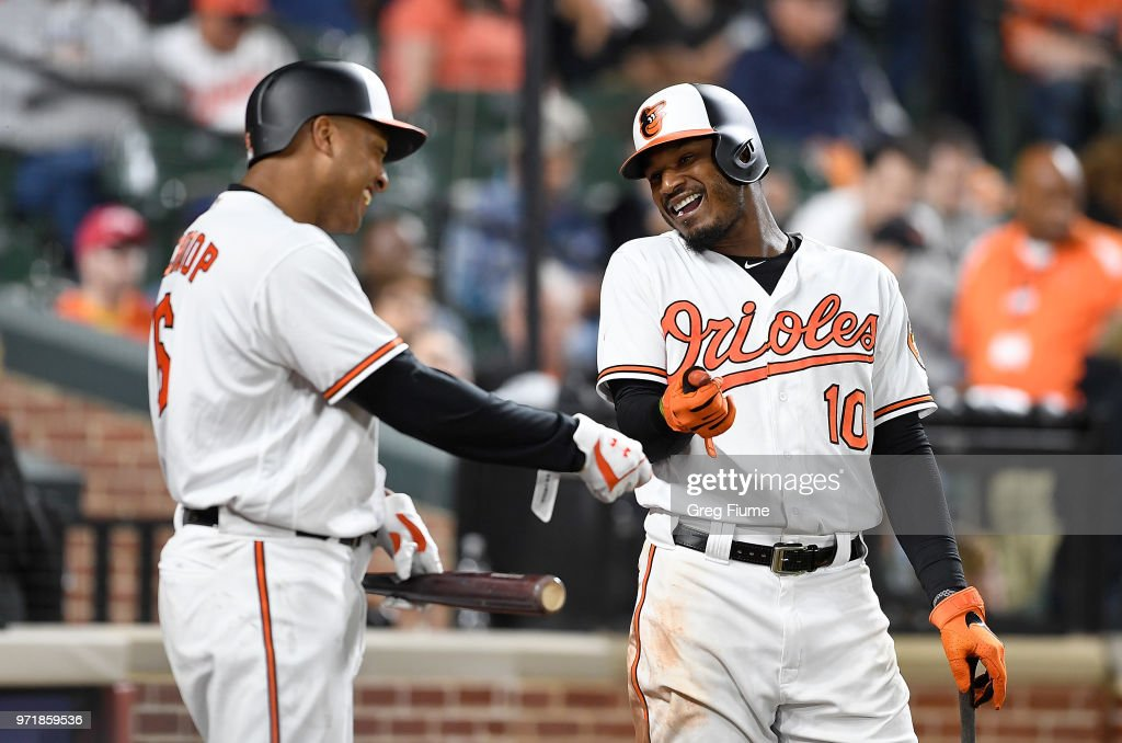 Jonathan Schoop #6 and Adam Jones #10 of the Baltimore Orioles talk during a pitching change in the seventh inning against the Boston Red Sox at Oriole Park at Camden Yards on June 11, 2018 in Baltimore, Maryland.
