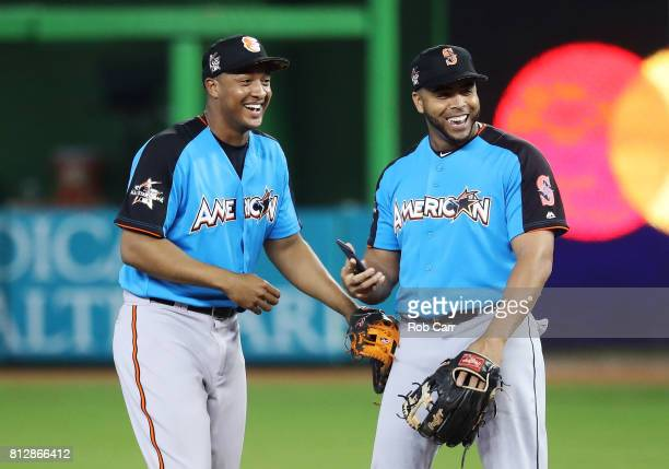 Jonathan Schoop of the Baltimore Orioles and the American League and Nelson Cruz of the Seattle Mariners and the American League joke during batting...