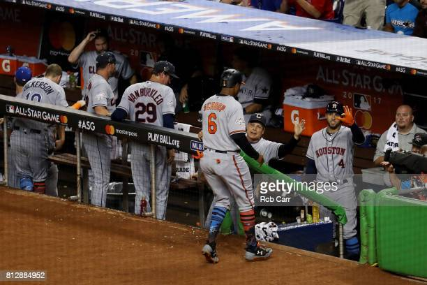 Jonathan Schoop of the Baltimore Orioles and the American League returns to the dugout after scoring a run on an RBI single by Miguel Sano of the...
