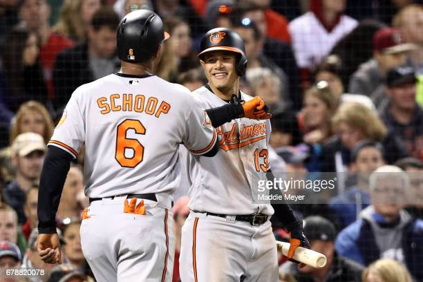 Jonathan Schoop of the Baltimore Orioles celebrates with Manny Machado after scoring a run against the Boston Red Sox during the fourth inning at...