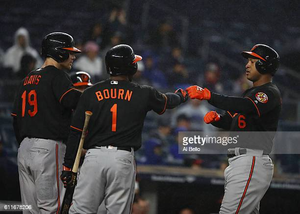 Jonathan Schoop of the Baltimore Orioles celebrates with Michael Bourn and Chris Davis after hitting a three run home run against the New York...