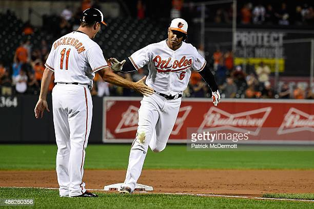 Jonathan Schoop of the Baltimore Orioles celebrates with third base coach Bobby Dickerson as he runs the bases after hitting a game tying tworun home...