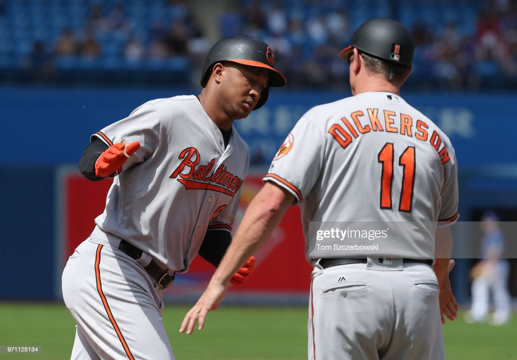 Jonathan Schoop #6 of the Baltimore Orioles is congratulated by third base coach Bobby Dickerson #11 after hitting a solo home run in the seventh inning during MLB game action against the Toronto Blue Jays at Rogers Centre on June 10, 2018 in Toronto, Canada.