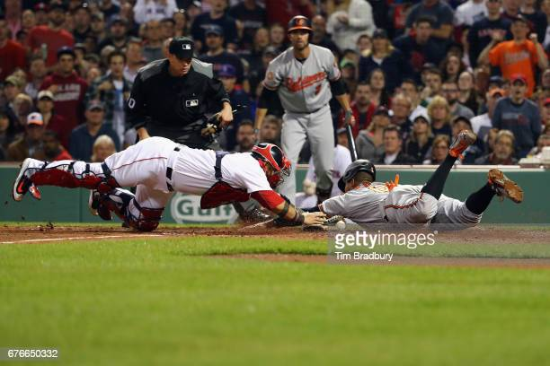 Jonathan Schoop of the Baltimore Orioles scores a run as Sandy Leon of the Boston Red Sox misses the tag after an RBI double by Trey Mancini of the...