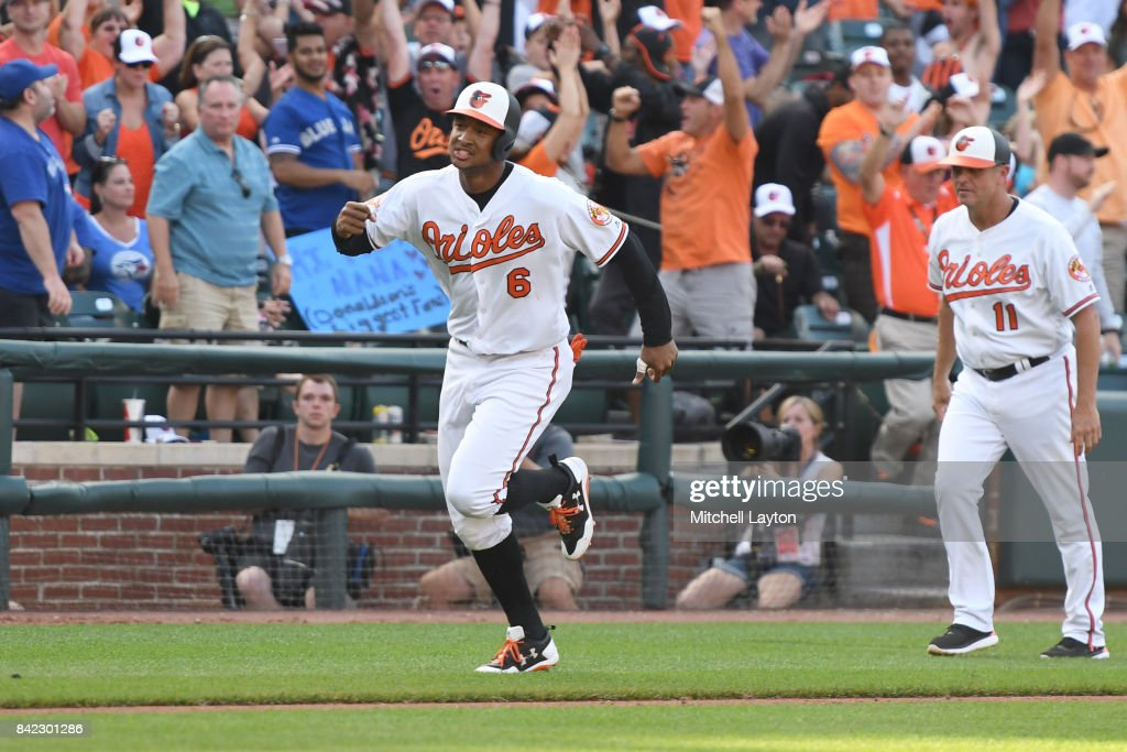 Jonathan Schoop #6 of the Baltimore Orioles scores the winning run on a Mark Trumbo #45 (not pictured) walk off single in the 12th inning during a baseball game against the Toronto Blue Jays at Oriole Park at Camden Yards on September 3, 2017 in Baltimore, Maryland.