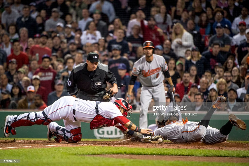 Jonathan Schoop #6 of the Baltimore Orioles slides as he evades the tag of Sandy Leon #3 of the Boston Red Sox to score during the fifth inning of a game on May 2, 2017 at Fenway Park in Boston, Massachusetts.